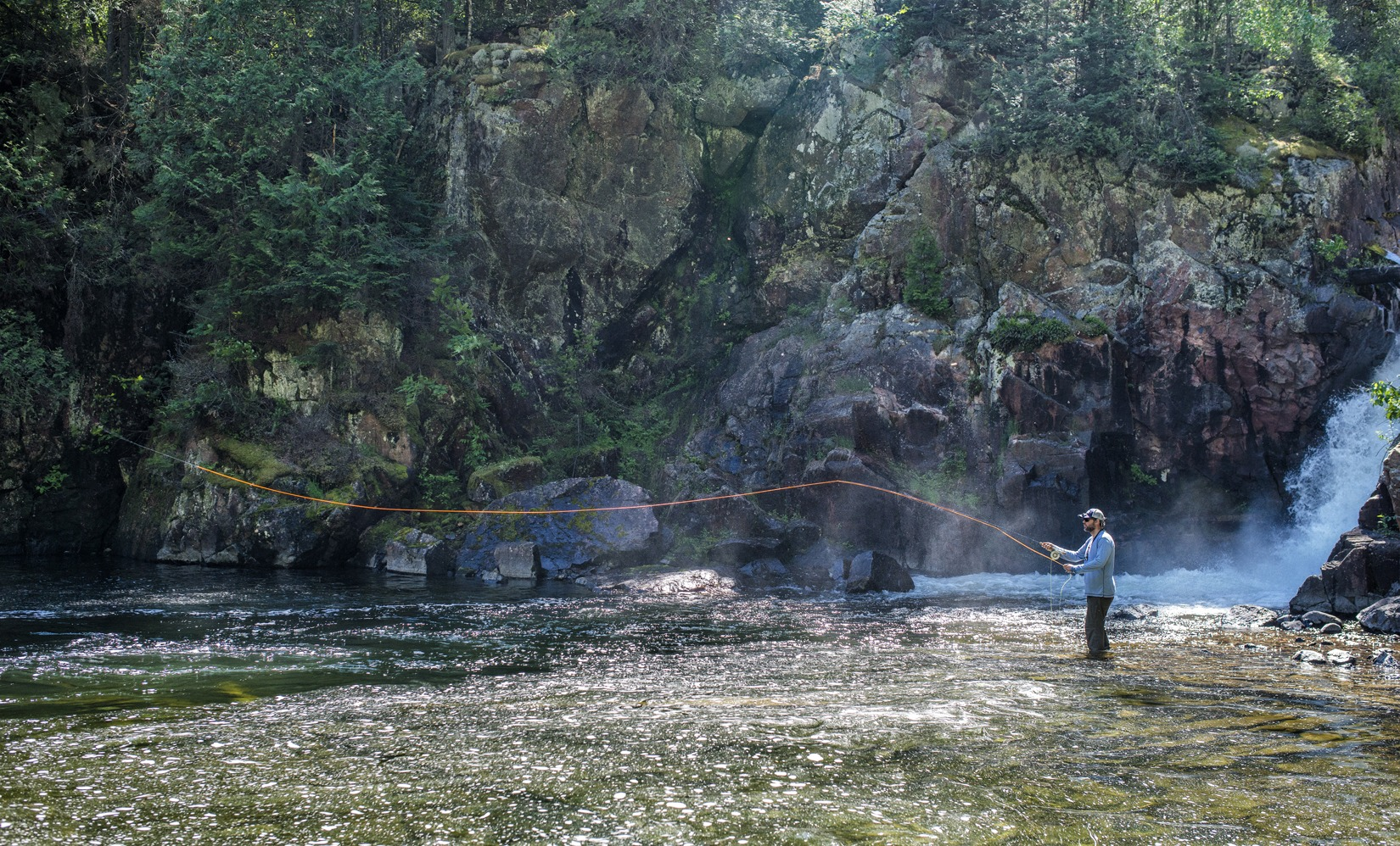 Fly fishing for trout at the waterfall